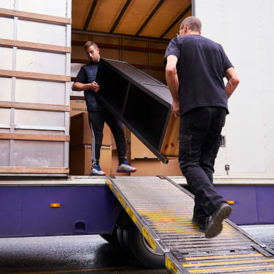 Two men loading furniture into a moving truck near A-American Self Storage in Lancaster, California
