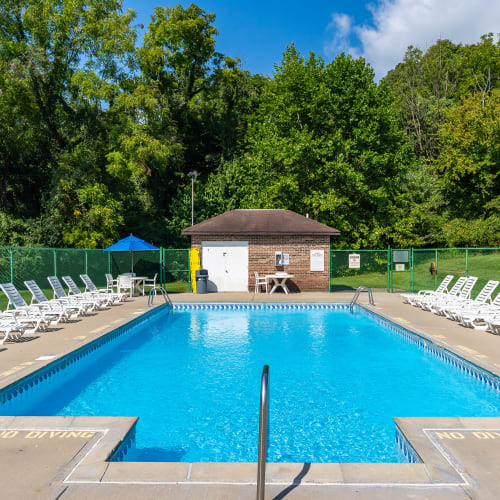 Swimming pool and sundeck lounge chairs at Indian Footprints Apartments in Harrison, Ohio