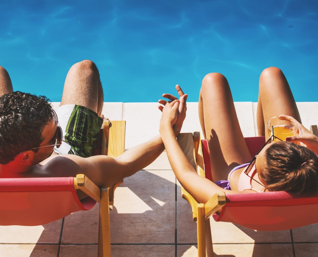 Couple relaxing by Vista Pointe Apartments' swimming pool in Santa Clara, California