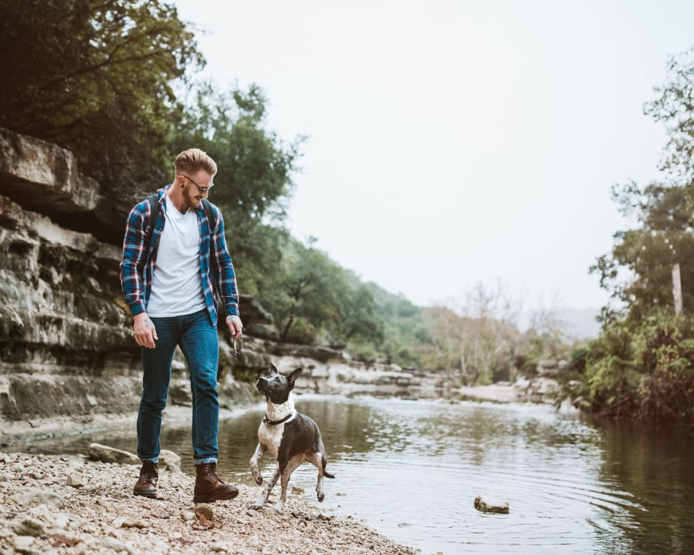 Resident out adventuring with his dog at a river near Beck at Wells Branch in Austin, Texas