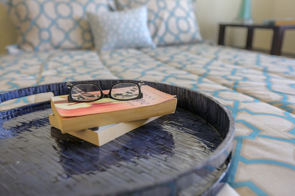 Books and reading glasses on a bed at Harmony at Spring Hill in Lorton, Virginia