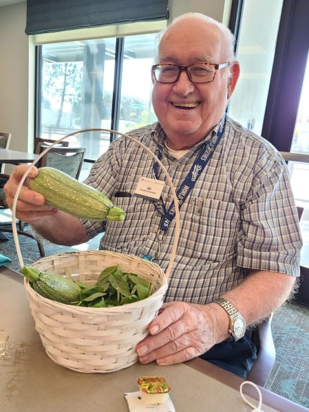 A West Covina resident shows off some fresh squash from the community garden.