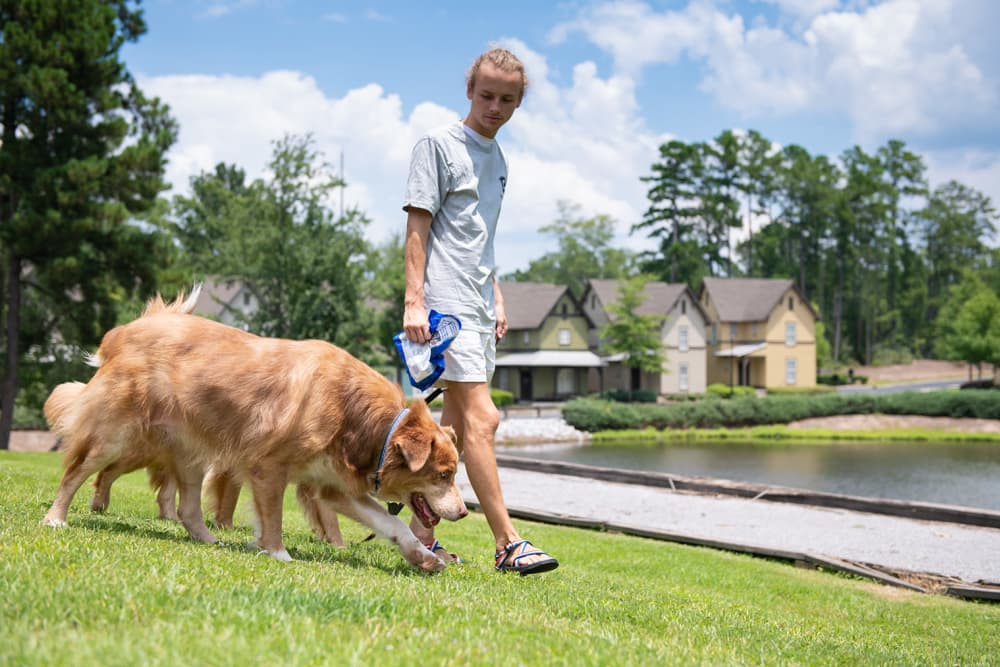Resident and dog walking at The Cottages of Hattiesburg in Hattiesburg Mississippi