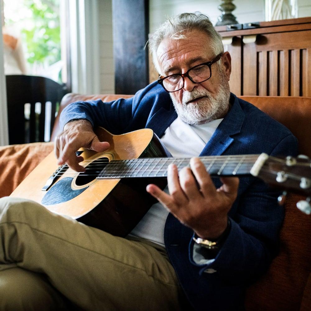 Senior man playing a guitar at Villa at the Lake in Conneaut, Ohio