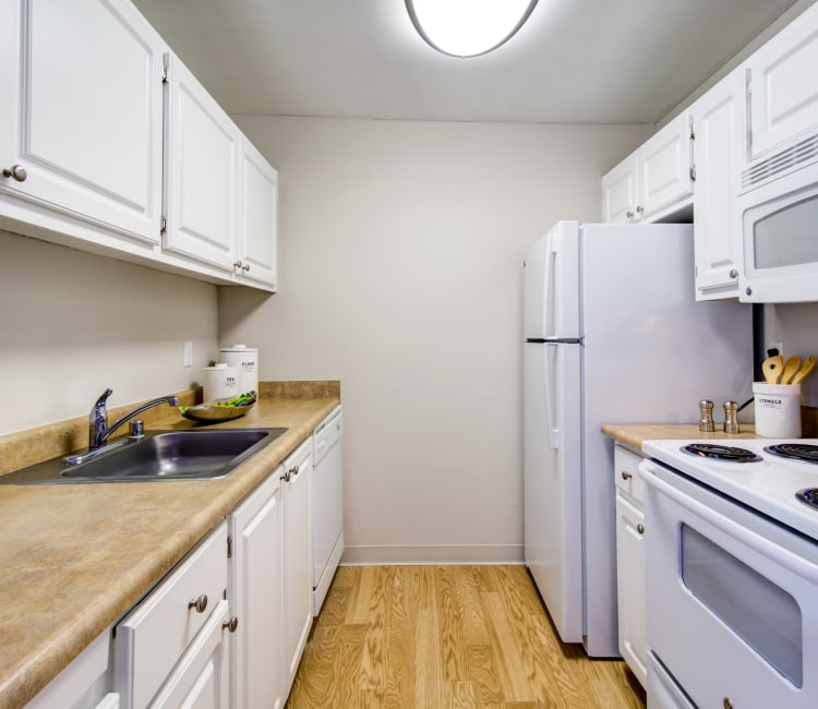 Modern kitchen with white appliances and hardwood flooring in a model home at Waterstone Fremont in Fremont, California