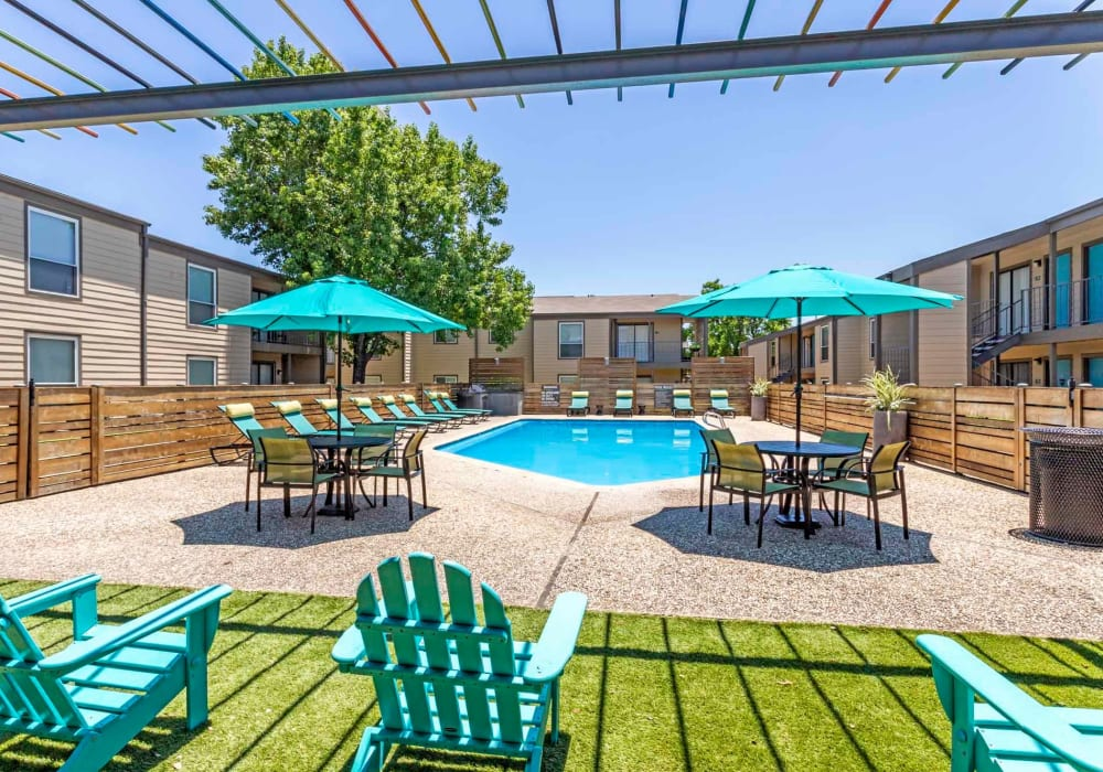 Patio seating by the pool at Sausalito Apartments in College Station, Texas