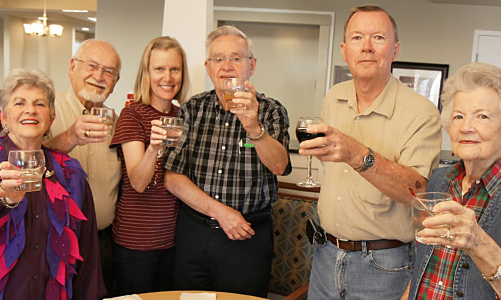 Group of colorfully dressed seniors toasting at MacArthur Hills in Irving, Texas