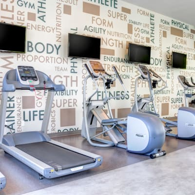 Cardio machines with individual flatscreen TVs in the onsite fitness center at Sofi Berryessa in San Jose, California