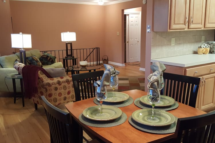 Model home dining area showing adjacent modern kitchen at Wingate Apartments