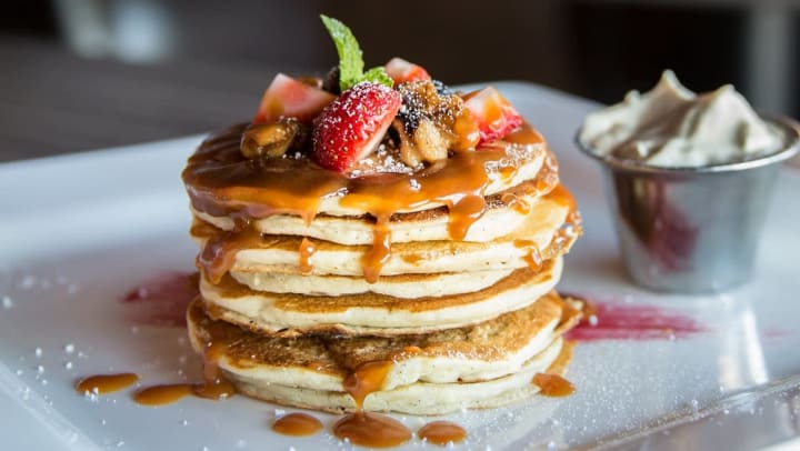 Plate of fruit-covered pancakes at a restaurant near Olympus 7th Street Station in Fort Worth, Texas