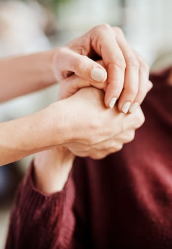 A staff member holding a resident's hand at Claiborne Senior Living.