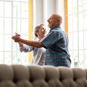 Two residents dancing in a lounge at Sunstone Village in Denton, Texas