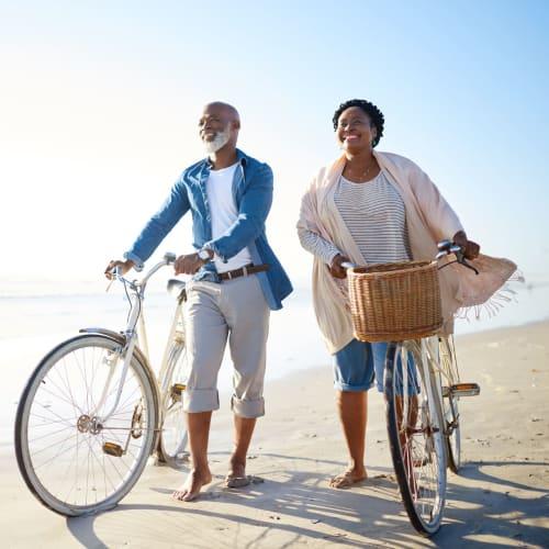 Resident couple walking their bikes on the beach near The Pointe at Siena Ridge in Davenport, Florida