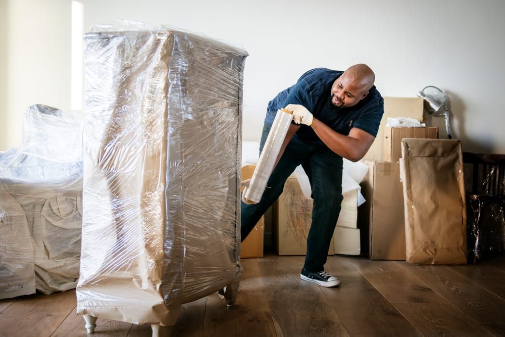 Man wrapping furniture to move near A-American Self Storage in Santa Fe Springs, California