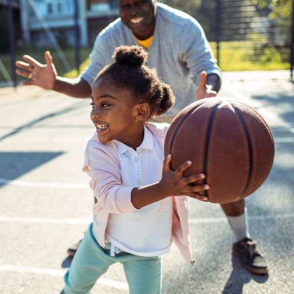 Father and daughter playing basketball on a court near at Olympus Grand Crossing in Katy, Texas