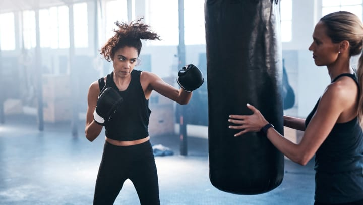 A woman with boxing gloves on punches a bag while another woman holds the bag stationary