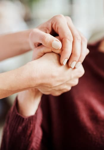 A staff member holding a resident's hand at The Claiborne at Gulfport Highlands in Gulfport, Mississippi.