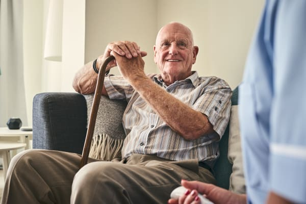 A senior resident sitting with a cane at Inglenook At Brighton in Brighton, Colorado