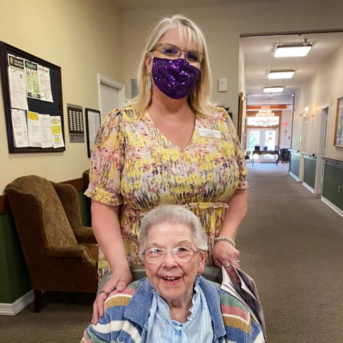 Masked caretaker with a resident at Canoe Brook Assisted Living in Duncan, Oklahoma