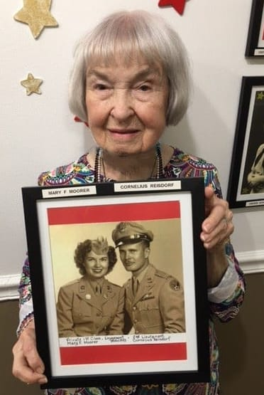 Mary, resident at Barkley Place, poses with a photo of her and her husband from their time in the military.