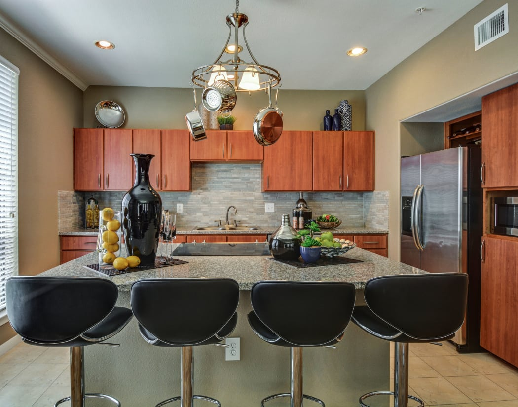 Beautiful gourmet kitchen with large island, granite countertops, and cherry wood cabinetry in model home at San Paloma Apartments in Houston, Texas