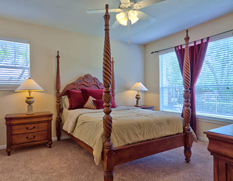 Master bedroom with plush carpeting and a ceiling fan at Somerset at Spring Creek in Plano, Texas