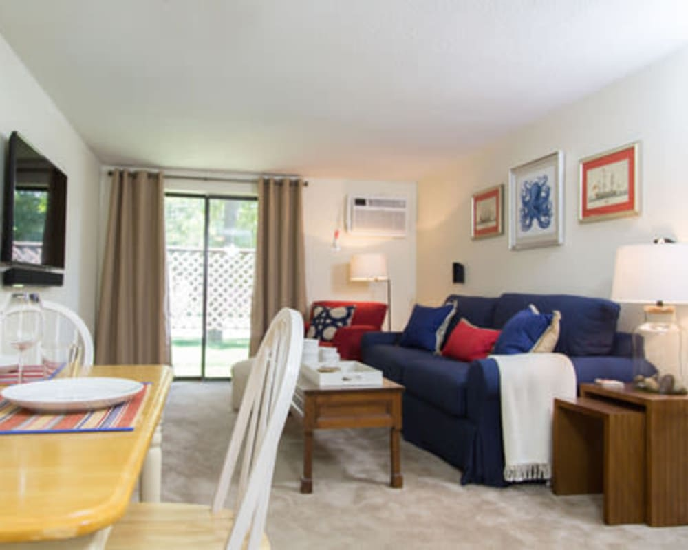 Living room with plush carpeting at London Court Apartments in Merrimack, New Hampshire