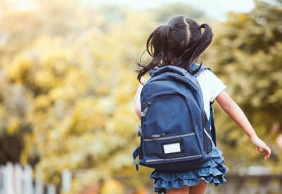 Resident child running to the bus stop for school at The Lakes of Schaumburg in Schaumburg, Illinois
