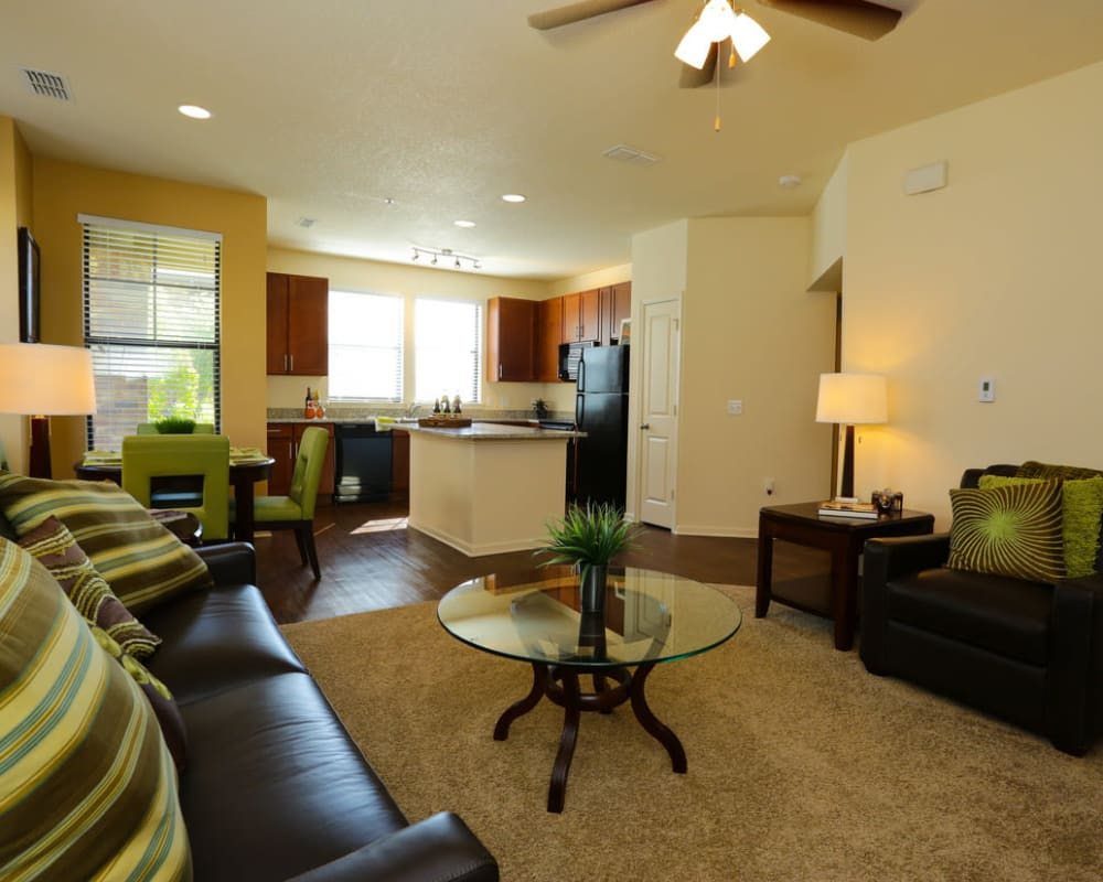 Large open-concept living area with plush carpeting in a model home at The Hawthorne in Jacksonville, Florida