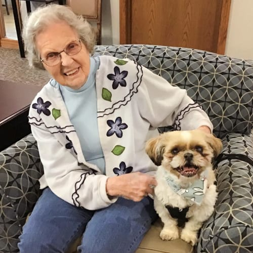 A happy resident with her dog at Oxford Senior Living in Wichita, Kansas