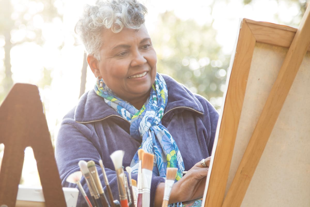 Resident painting a picture on an easel at Oak Terrace Memory Care in Soulsbyville, California