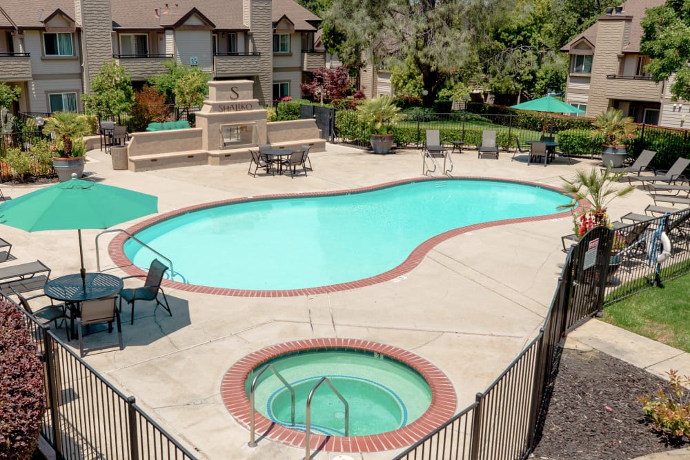 Spacious sundeck with table and chairs next to a swimming pool at Shaliko in Rocklin, California