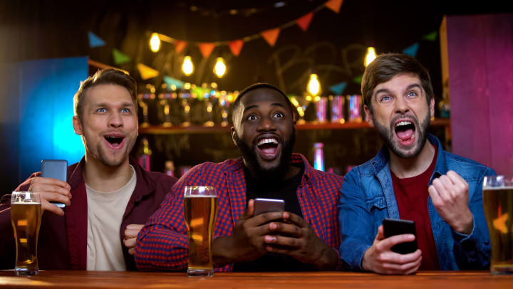 Three men sitting at a bar with beers, cheering.