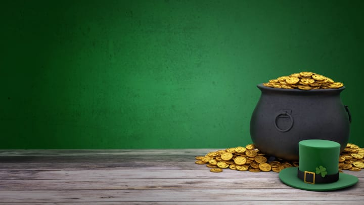 Pot of gold, a pile of gold coins, and green leprechaun hat sitting on a wooden floor with a green wall in the background
