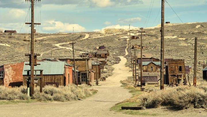 A long, wavy, dirt road runs through a small, abandoned town.