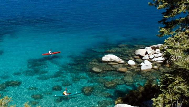 Two people sitting in kayaks paddling on water that is clear and blue.