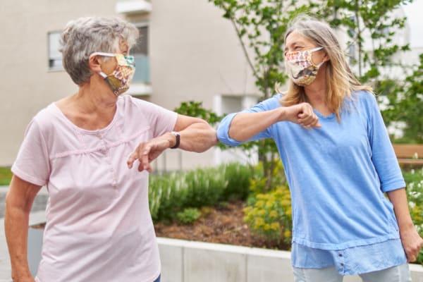 Senior ladies in masks touching elbows