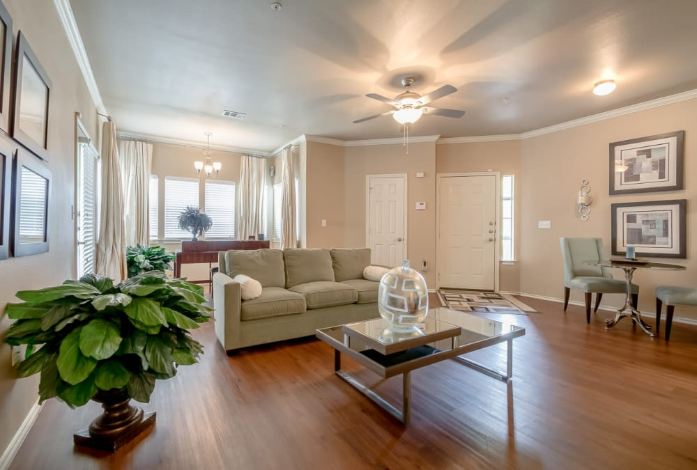 Open-concept floor plan with hardwood floors and accent wall in the living area of model home at Alon at Castle Hills in San Antonio, Texas