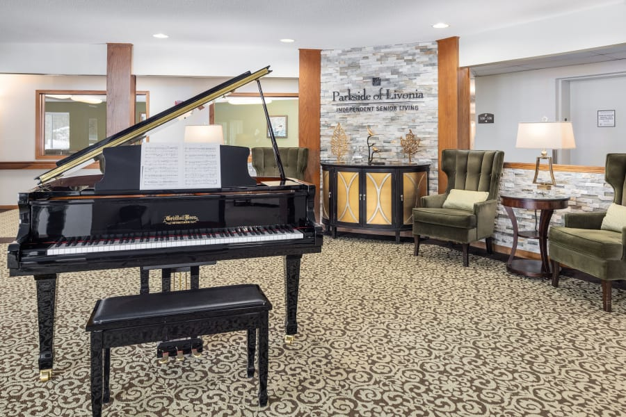 Elegant lobby with a baby grand piano at Parkside of Livonia in Livonia, Michigan