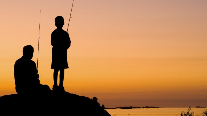 A silhouette of a man and his son fishing during a sunset