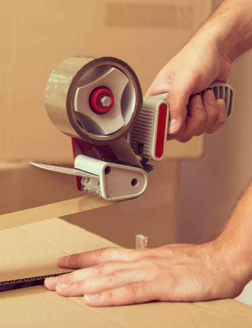 A man uses a tape dispenser to safely seal a box, which he'll store at Storage World in Sinking Spring, Pennsylvania