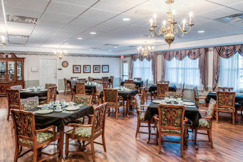Ornate communal dining area with wood accents and chandeliers at Grand Victorian of Sycamore in Sycamore, Illinois