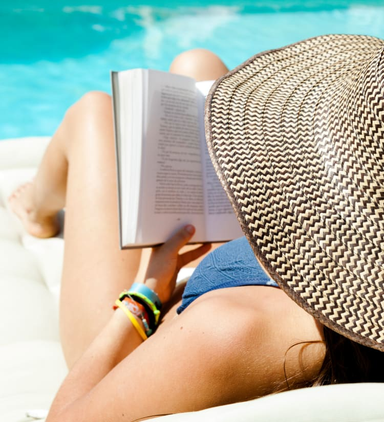 Resident reading a book on a chaise lounge chair by the swimming pool at Magnolia on the Green in Allen, Texas