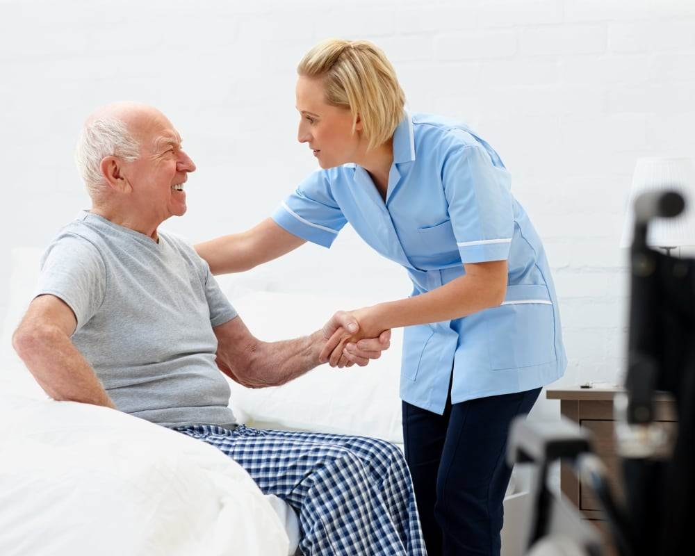 Staff helps resident out of bed at Willows Landing in Monticello, Minnesota.