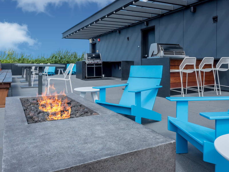 Patio seating with a cozy fire pit at Rooster Apartments in Seattle, Washington