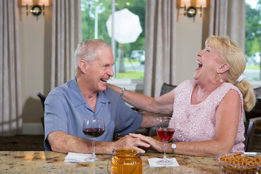 Older couple laughing while drinking beer and eating pretzels in  Bonita Springs