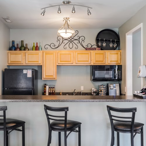 Clubhouse kitchen with counter seating at Indian Footprints Apartments in Harrison, Ohio
