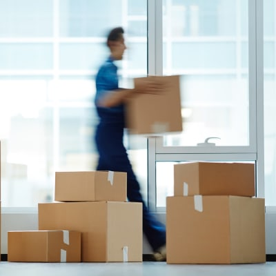 Person carrying a box past stacked moving boxes at A-American Self Storage in Pomona, California