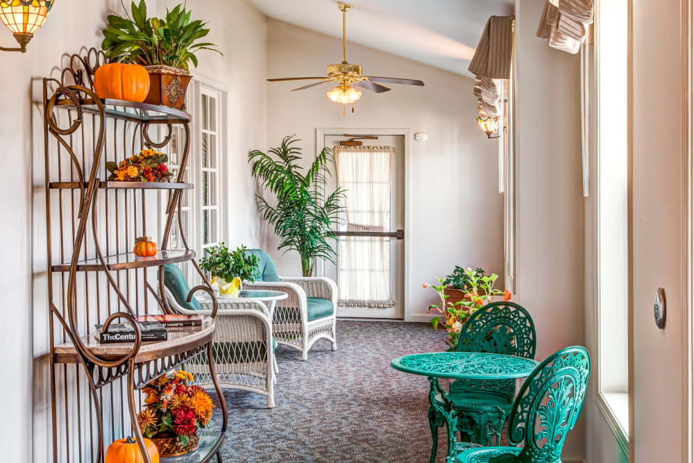 Charming sunroom with elegant green patio chairs and table at Grand Victorian of Sycamore in Sycamore, Illinois