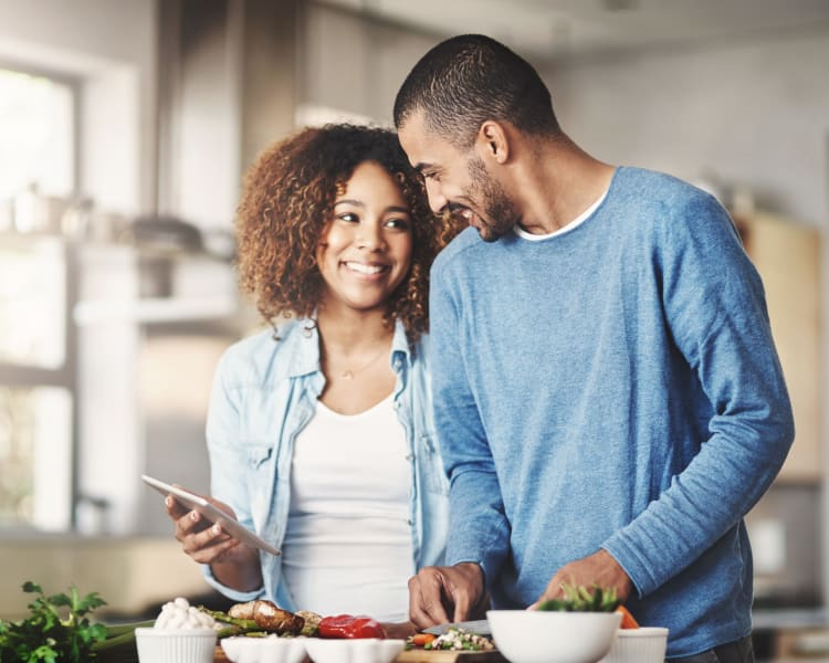 Resident couple looking up a recipe on a tablet while they cook a fresh meal in their new home at Sofi at Topanga Canyon in Chatsworth, California